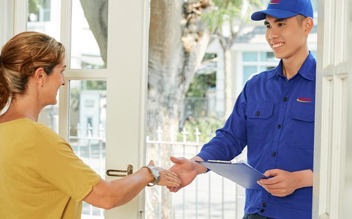 pest control technician greeting homeowner at front door