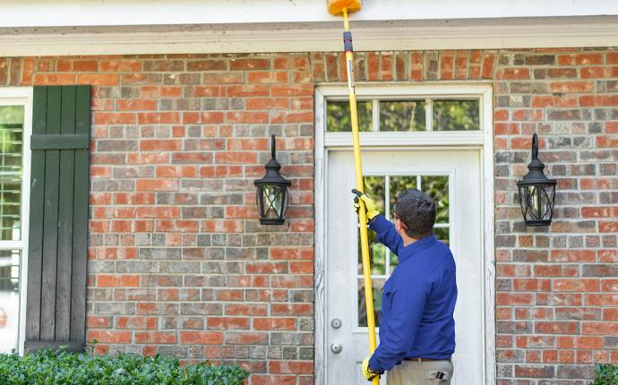 a pest expert removing spider webs outside a home