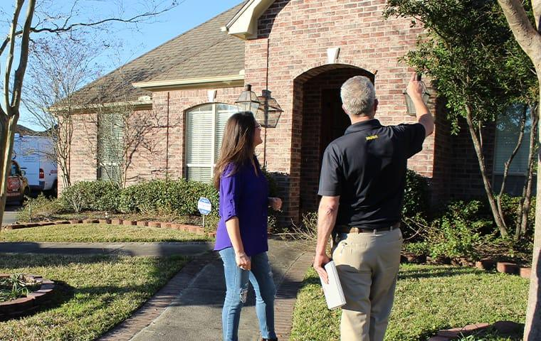 a pest control technician and a homeowner inspect the exterior of a home in anahuac texas