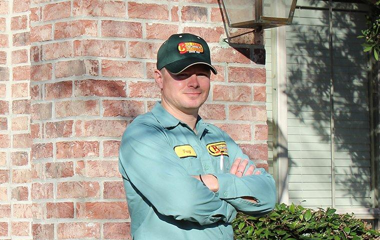 a pest expert in front of a home