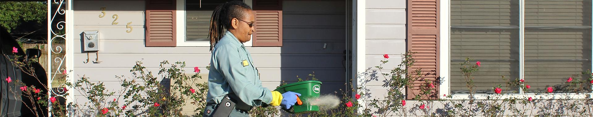 bill clark pest control technician treating yard for fire ants
