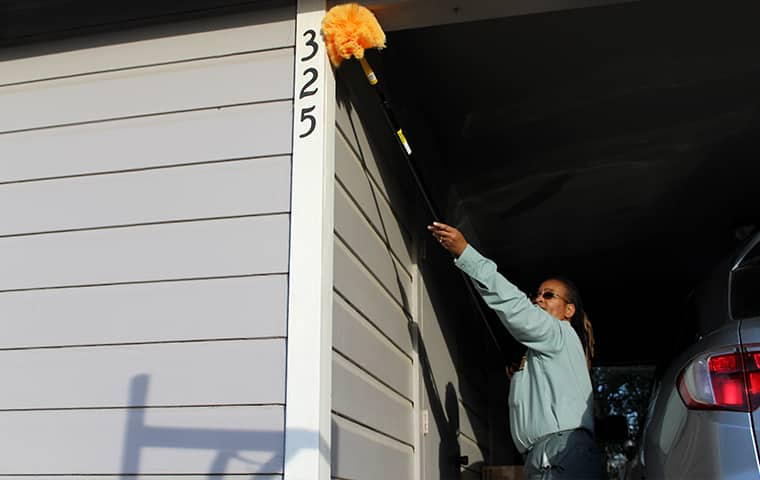 a bill clark bugsperts service technician performing dewebbing services on the exterior of a home in lumberton texas