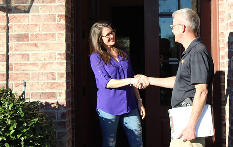 a bill clark bugsperts service technician with a residential homeowner at a home in lumberton texas