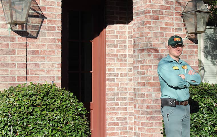 a bill clark bugsperts service technician posing outside of a home in vidor texas