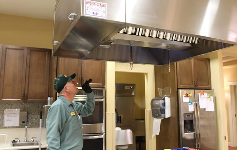 a pest control technician inspecting a commercial kitchen in mauriceville texas