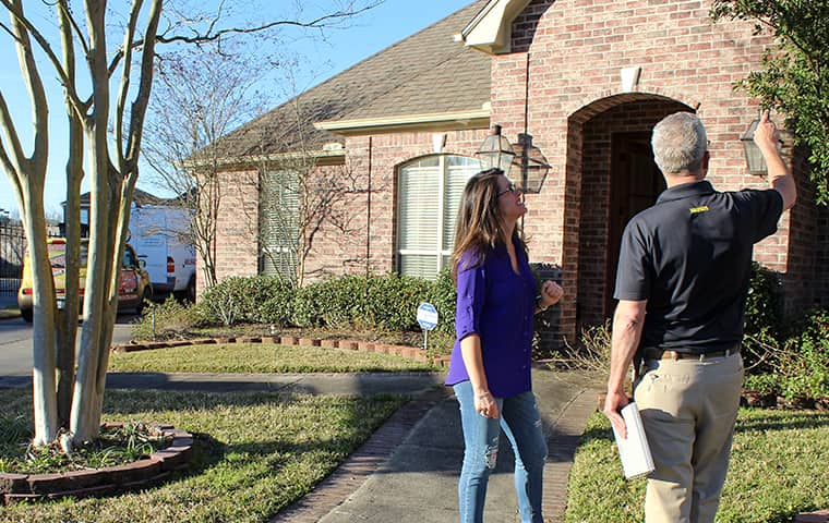 pest control technician and homeowner discuss pest control options outside a home in montgomery texas