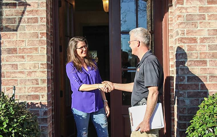 homeowner and pest control technician greeting each other at nederland texas home