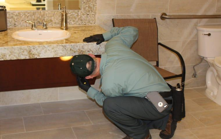 a bill clark pest control technician inspecting for pests in a sabine pass commercial business bathroomtexas
