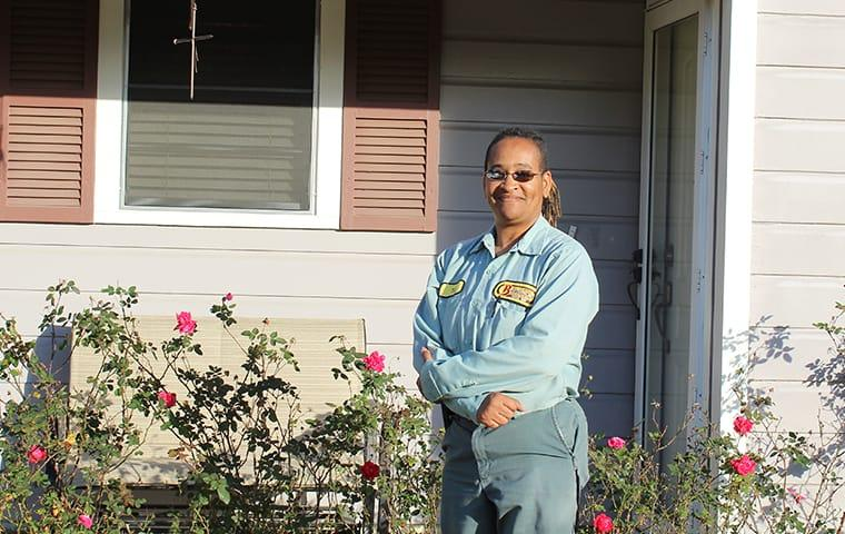 a pest control technician standing in front of a home in sabine pass, texas