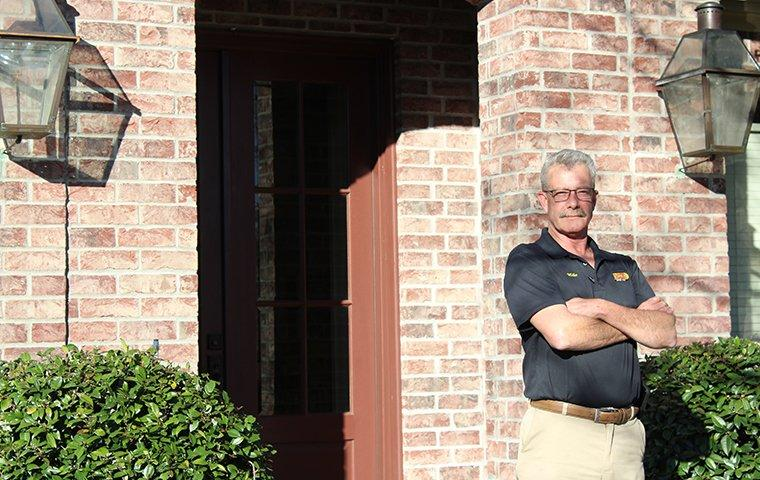 a technician standing outside a home in wallisville texas