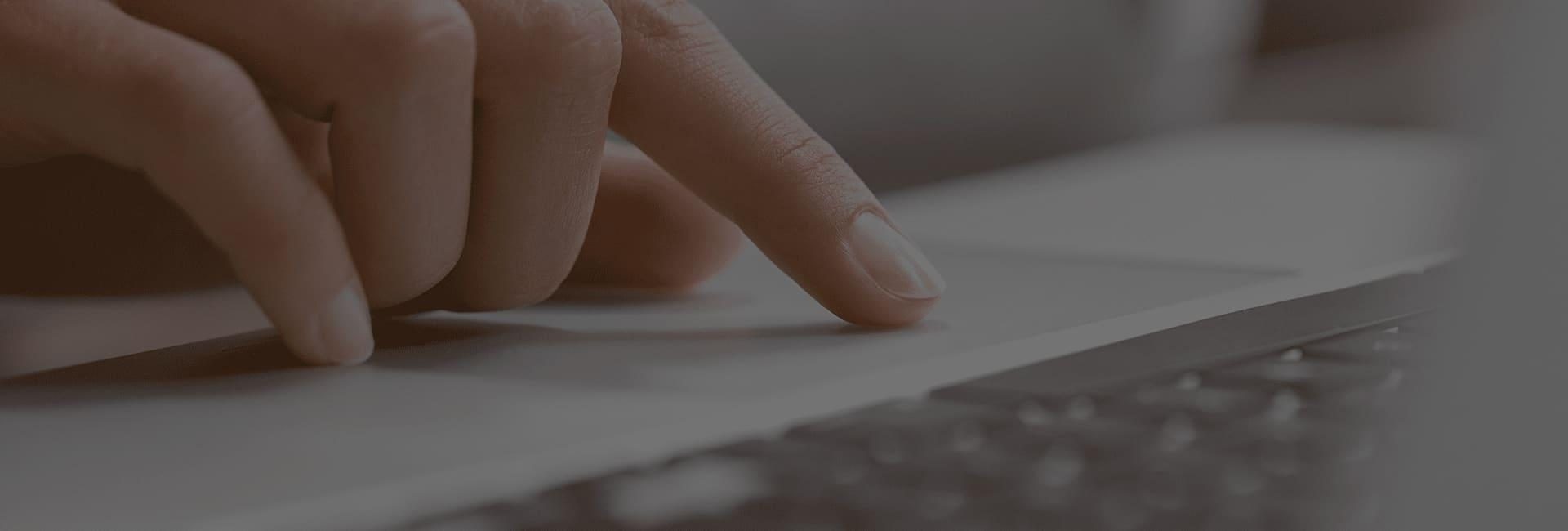 a finger moving across the mousepad on a laptop