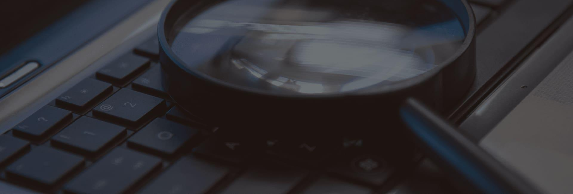 a magnifying glass laying on top of a keyboard