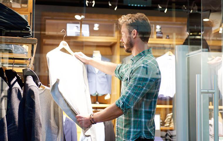 man looking at shirts at a store in oklahoma city