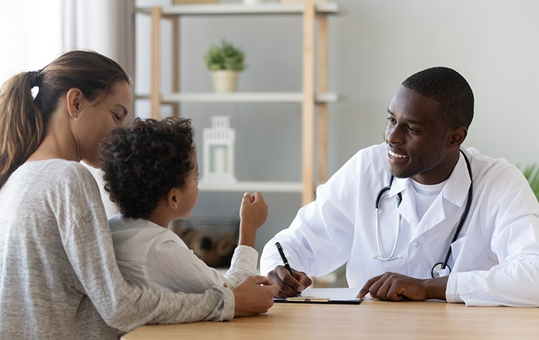 a doctor meeting with a child and mother inside a medical facility