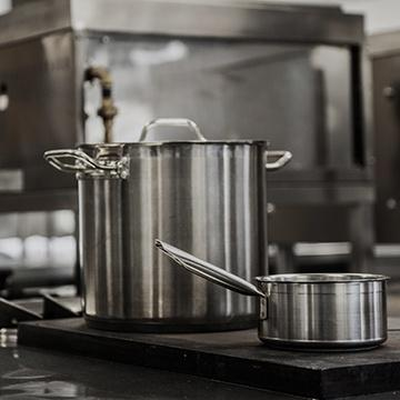 a pot and pan on a stove in a commercial kitchen