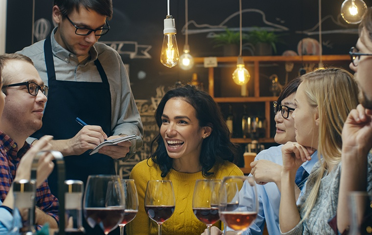 a happy group of friends and a waiter inside a restaurant