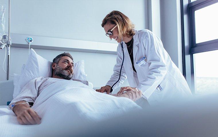 a nurse helping a man in a hospital bed