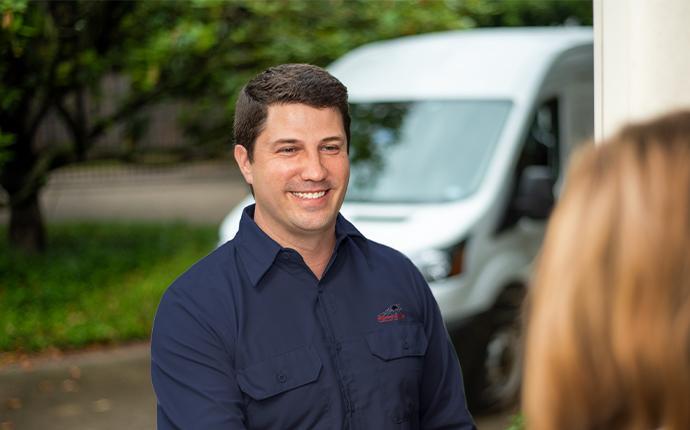 pest control technician greeting customer