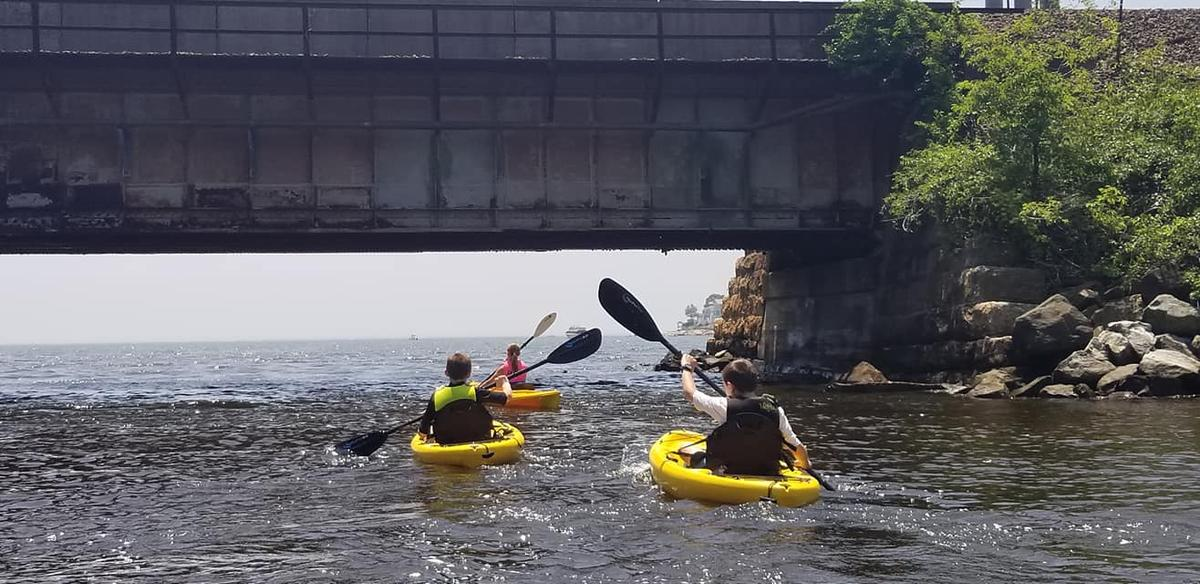 Two kayakers pass underneath a railroad bridge