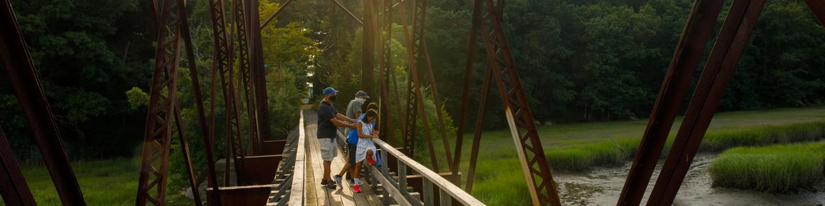 A family looks out at a wetland from an iron and wood bridge