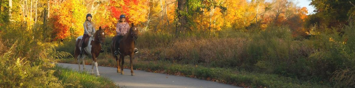 Two women ride their horses on a paved path surrounded by fall colors.