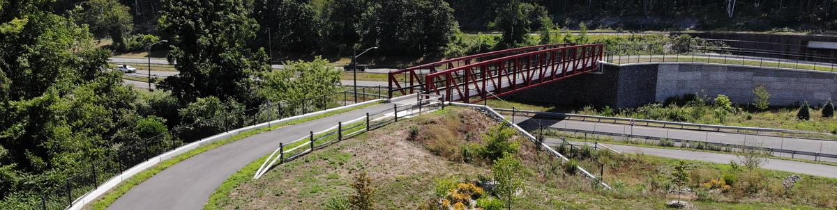 A paved multi-use path curves to reach an overpass