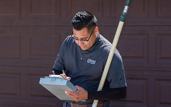 pest control technician inspecting exterior