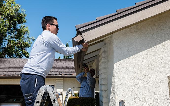 technician repairing termite damage on house