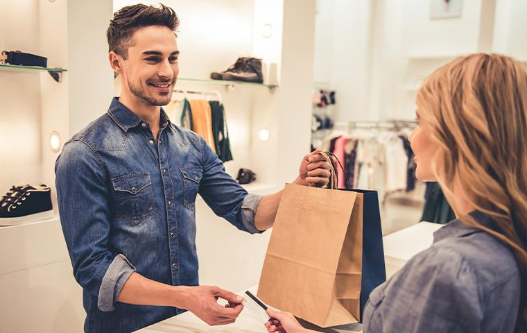 sales associate handing bag to customer