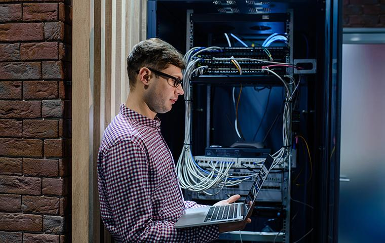 man looking at a laptop in a server room