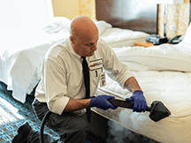 a service technician treating a bed for bed bugs