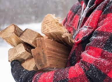 man carrying firewood in the snow