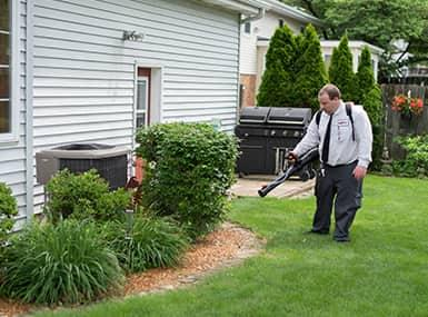 a professionial pest control technician treating a streater home in order to reduce the mosquito infestation this summer