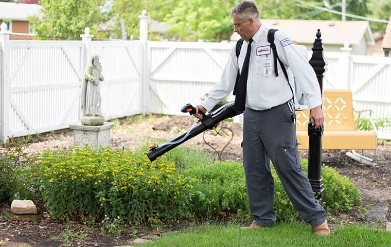 professional pest control technician treating a quad city yardfor mosquito control