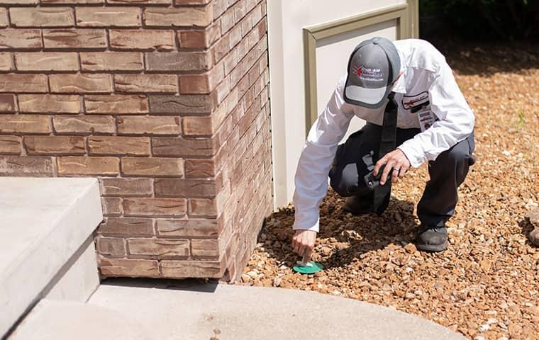 a professional pest control technician from quik kill pest eliminators applying termites control solution to a quad city home