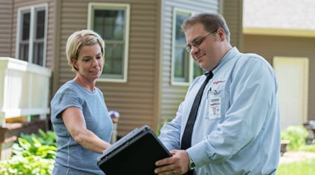 a pest technician speaking to a homeowner in rock island illinois
