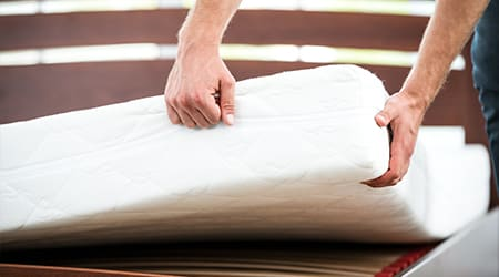 a person putting a cover on a mattress in geneseo illinois