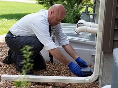 a technician setting up a rodent trap outside a home in peoria illinois