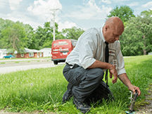 a technician inspecting a termite baiting system in a yard