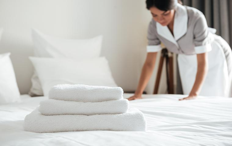 cleaning lady making the hotel bed