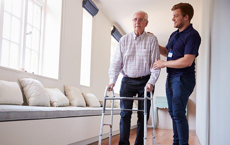 a male nurse helping an elderly man in a retirement home