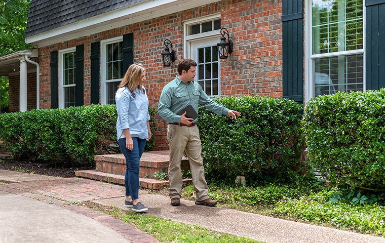 a pest technician inspecting with homeowner