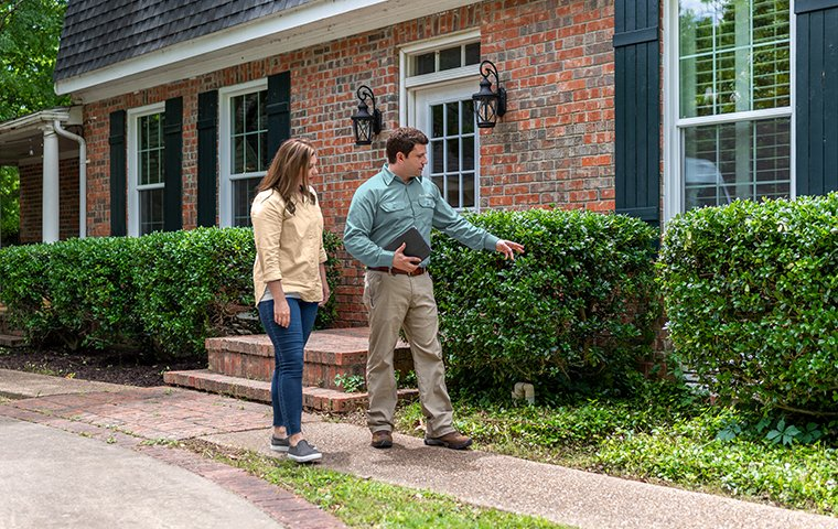 a pest technician inspecting with a homeowner