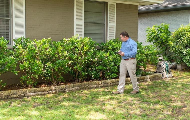 a technician inspecting the outside of a house in modesto california