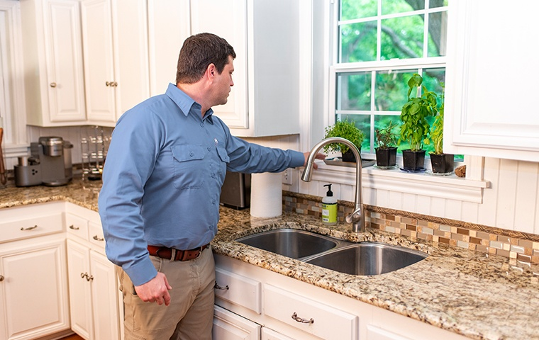 a pest technician inspecting the kitchen of a home in modesto california