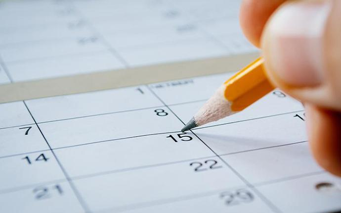 person marking a date on a calendar