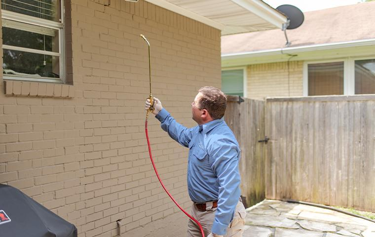 technician treating exterior of a home