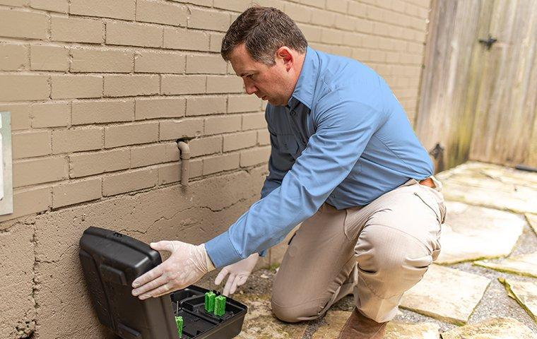 a pest technician checking a rodent trap outside of a home in modesto california