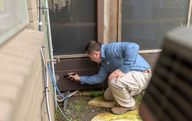 a pest technician inspecting the exterior of a home for termites in modesto california