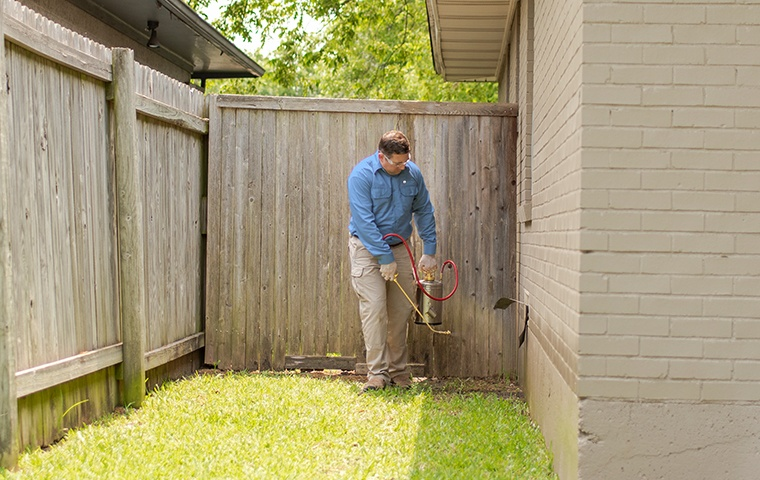 a pest technician performing an exterior treatment at a home in modesto california